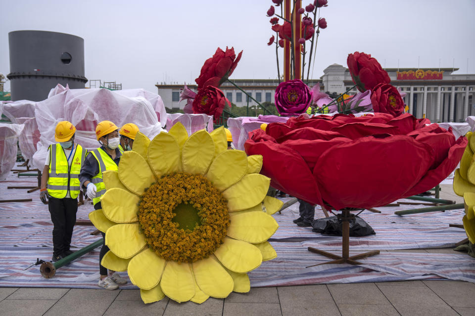 """FILE - In this Sept. 18, 2021, file photo, workers move a giant flower blossom as part of preparations for China's National Day holiday on Tiananmen Square in Beijing. China's """"zero tolerance"""" strategy of trying to isolate every case and stop transmission of the coronavirus has kept kept the country where the virus first was detected in late 2019 largely free of the disease. (AP Photo/Mark Schiefelbein, File)"""