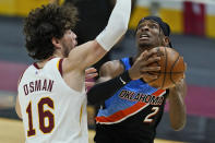 Oklahoma City Thunder's Shai Gilgeous-Alexander (2) drives to the basket against Cleveland Cavaliers' Cedi Osman (16) in the second half of an NBA basketball game, Sunday, Feb. 21, 2021, in Cleveland. (AP Photo/Tony Dejak)