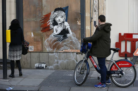 People photograph a new graffiti mural attributed to Banksy, opposite the French embassy in London, Britain January 25, 2016.  REUTERS/Stefan Wermuth