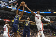 Indiana Pacers forward T.J. Warren (1) pulls down a rebound in front of Miami Heat center Bam Adebayo (13) during the first half of an NBA basketball game in Indianapolis, Wednesday, Jan. 8, 2020. (AP Photo/AJ Mast)