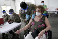 Loida Mendez, 86, gets the first dose of the Pfizer COVID-19 vaccine from U.S. Army medic Luis Perez, at a FEMA vaccination site at Miami Dade College, Wednesday, March 3, 2021, in North Miami, Fla. This is one of four FEMA sites in Florida that opened Wednesday with capacity to vaccinate up to 3,000 people a day, seven days a week. (AP Photo/Marta Lavandier)
