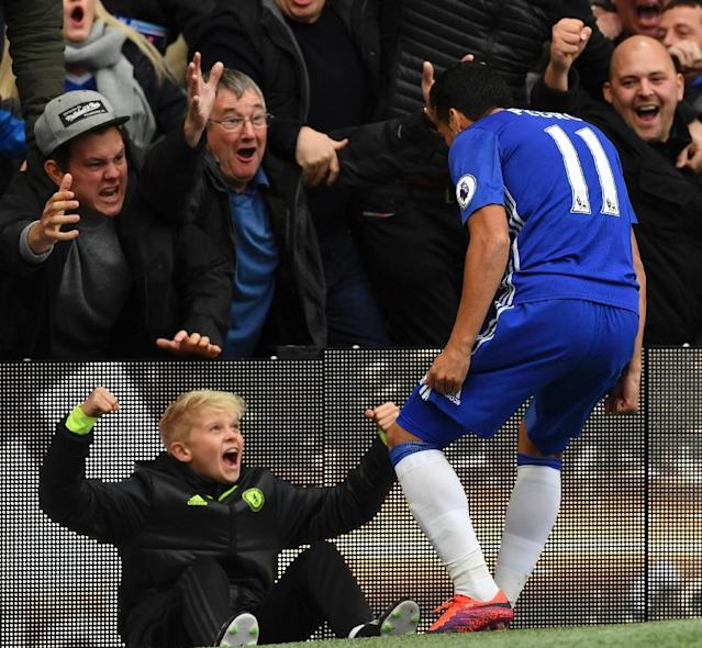Chelsea's midfielder Pedro celebrates with ball-boy and supporters after scoring against Manchester United at Stamford Bridge in London on October 23, 2016 (AFP Photo/Ben Stansall)