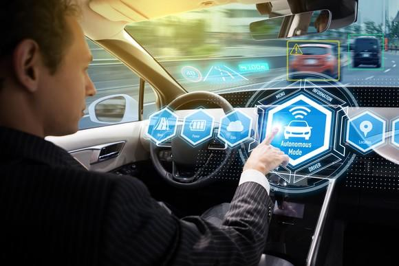 Man activating self-driving mode on car
