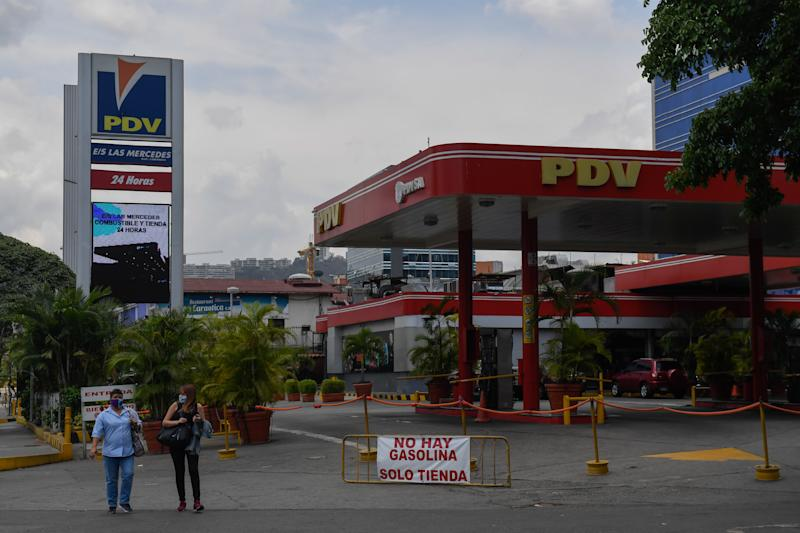People walk pass a gas station with a sign reading 'No gasoline. Only store' due to the lack of oil in Caracas, on May 14, 2020 amid the novel coronavirus (COVID-19) outbreak. - Maduro's government claims to have contained the spread of the new coronavirus in Venezuela, but maintains without changes the quarantine declared two months ago. According to analysts, the reason goes beyond the pandemic: an aggravated gasoline shortage that prevents reactivating the economy. (Photo by Federico PARRA / AFP) (Photo by FEDERICO PARRA/AFP via Getty Images)