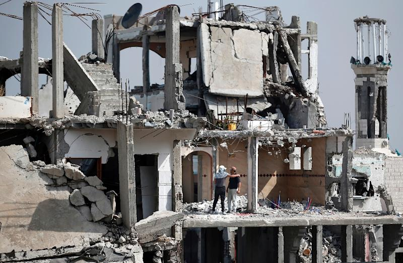 Palestinian workers clear the rubble of a heavily damaged building on April 15, 2015 in the eastern Gaza City neighborhood of Shejaiya which was destroyed during the 50-day war between Israel and Hamas militants