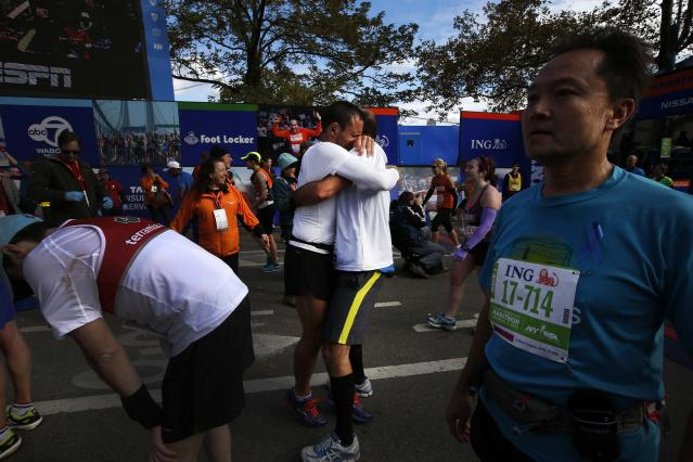 Two runners embrace after crossing the finish line of the New York City Marathon in New York, November 3, 2013. More than 45,000 competed in the event which winds its way through the five New York City boroughs finishing in Central Park. REUTERS/Mike Segar (UNITED STATES - Tags: SPORT ATHLETICS)