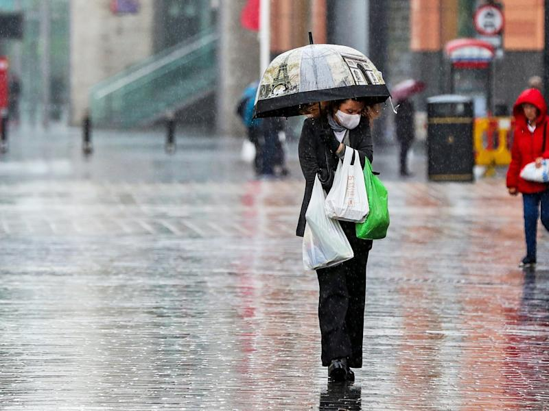 A shopper walks through the rain with an umbrella on 5 June, 2020: Peter Byrne/PA Wire