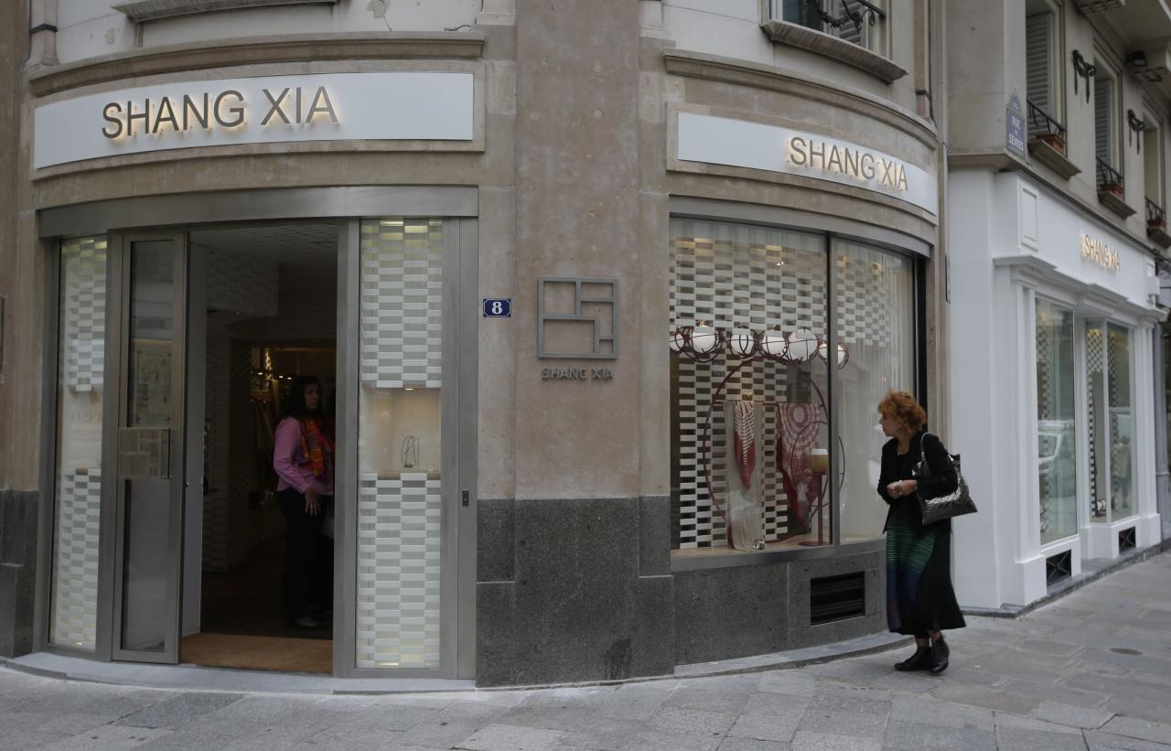 A woman walks past the shop of the young brand Shang Xia on its opening day in Paris September 11, 2013. Shang Xia, the Chinese-born brand backed by French luxury goods group Hermes, opened its first shop outside its home market in Paris on Wednesday to test appetite among non-Chinese customers for its handcrafted products. The brand is trying to build a business centred on the revival of traditional Chinese crafts such as porcelain, cashmere felt and furniture, that were all but nearly destroyed by China's proletarian Cultural Revolution. REUTERS/Jacky Naegelen (FRANCE - Tags: FASHION BUSINESS)