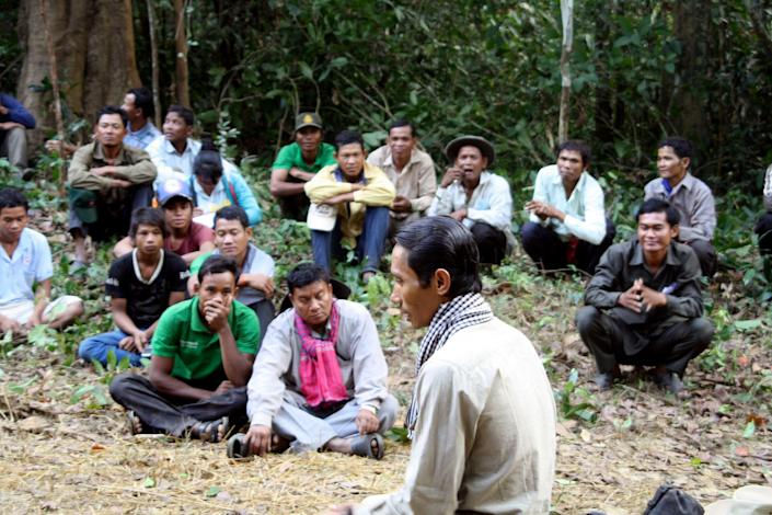In this photo taken May 30, 2008 and released by The Cambodian Center for Human Rights (CCHR), Chut Wutty, foreground, sits with logging workers in a jungle of Stung Treng province in northeastern of Phnom Penh, Cambodia. The environmental watchdog was shot by a military policeman in April as he probed logging operations in one of the country's last great forests. (AP Photo/The Cambodian Center for Human Rights)
