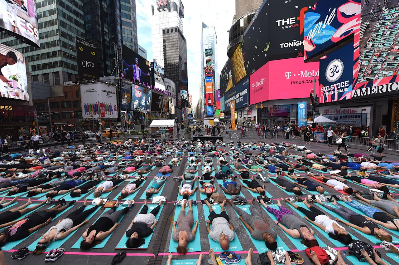 <p>People take part in the 15th annual Times Square yoga event celebrating the Summer Solstice, the longest day of the year, during classes in the middle of Times Square on June 21, 2017 in New York. (Photo: Timothy A. Clary/AFP/Getty Images) </p>