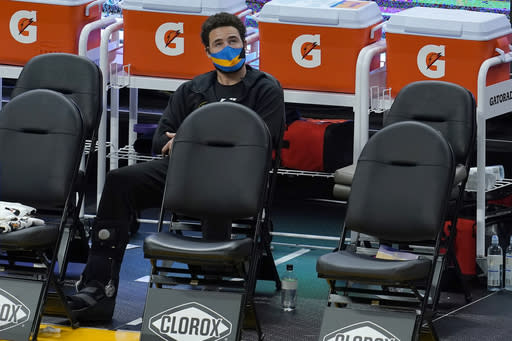 Injured Golden State Warriors guard Klay Thompson sits on the sideline during the second half of the team's NBA basketball game against the Indiana Pacers in San Francisco, Tuesday, Jan. 12, 2021. (AP Photo/Jeff Chiu)