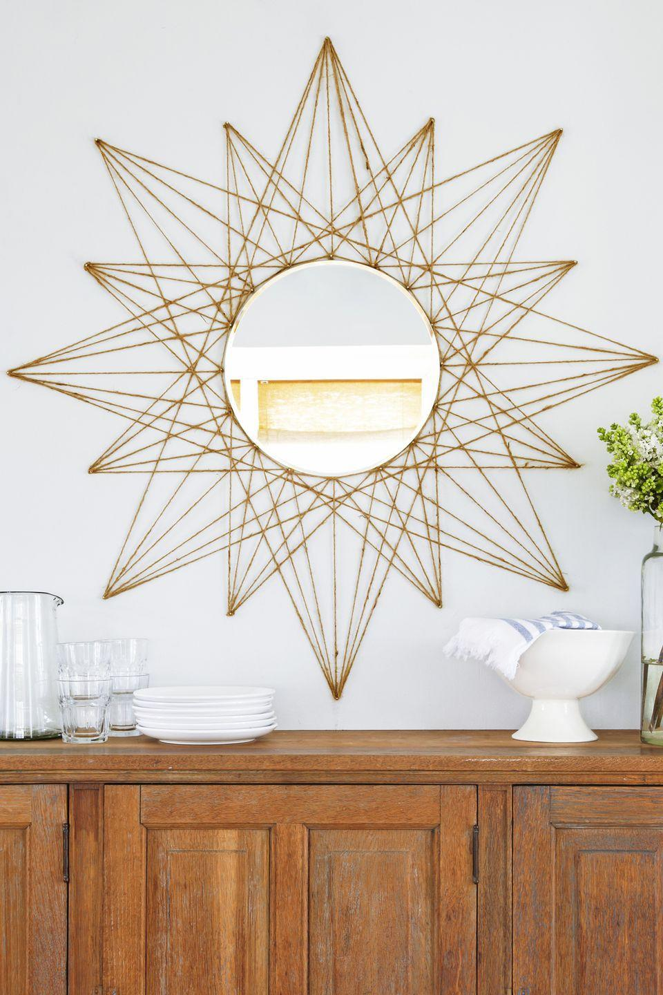"""<p>This stunning star mirror looks intricate, but it's surprisingly easy to DIY if you follow the step-by-step guide. An added bonus: It costs less than $25 to make. </p><p><em><a href=""""https://www.goodhousekeeping.com/home/decorating-ideas/a47625/diy-rope-star-mirror/"""" rel=""""nofollow noopener"""" target=""""_blank"""" data-ylk=""""slk:Get the tutorial »"""" class=""""link rapid-noclick-resp"""">Get the tutorial »</a></em></p>"""