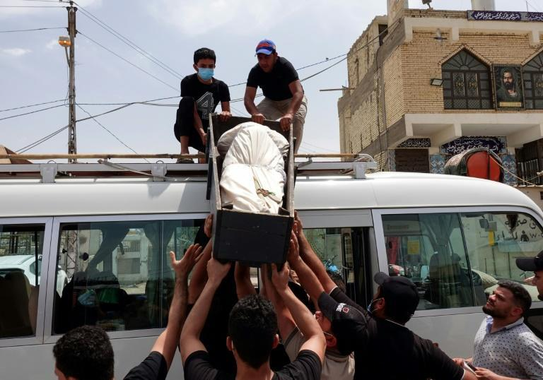 Iraqis transport the coffin of a relative killed during the hospital fire