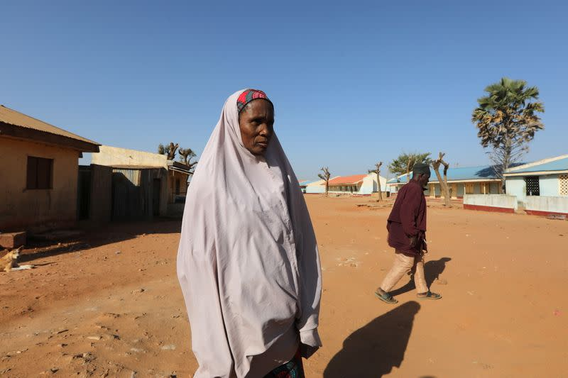 A woman stands near Government Science school where gunmen abducted students, in Kankara