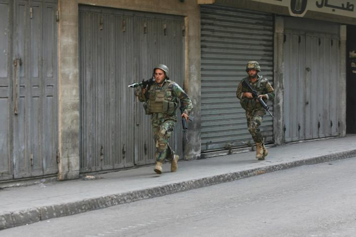 Lebanese armed forces run on a street during an assault on Islamist gunmen's makeshift positions in Tripoli, on October 25, 2014 (AFP Photo/Ghassan Sweidan)