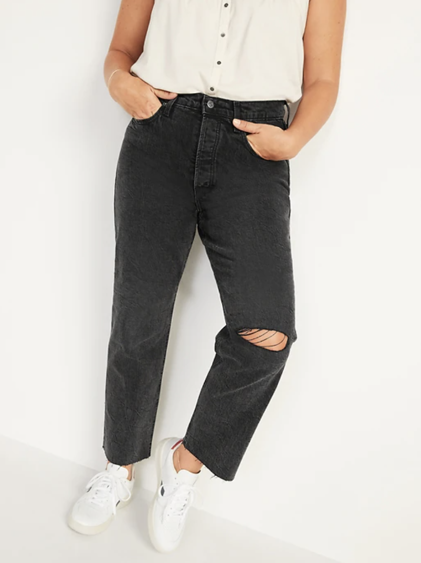 model wearing Extra High-Waisted Button-Fly Sky-Hi Straight Black Ripped Jeans and white sneakers