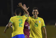 Brazil's Roberto Firmino, right, celebrates with teammate Brazil's Danilo after scoring his side's opening goal against Venezuela during a qualifying soccer match for the FIFA World Cup Qatar 2022 in Sao Paulo, Brazil, Friday, Nov.13, 2020. (Nelson Almeida/Pool via AP)