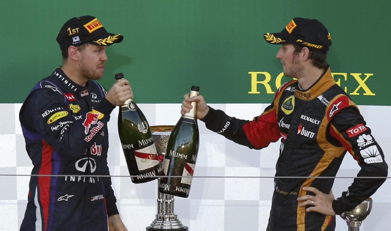 Red Bull Formula One driver Sebastian Vettel (L) of Germany toasts third-placed Lotus Formula One driver Romain Grosjean of France on the podium after winning the Japanese F1 Grand Prix at the Suzuka circuit October 13, 2013. REUTERS/Toru Hanai (JAPAN - Tags: SPORT MOTORSPORT F1)