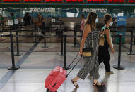 A pair of masked travelers head to the ticketing counter for Frontier Airlines in the main terminal of Denver International Airport Wednesday, July 22, 2020, in Denver. (AP Photo/David Zalubowski)