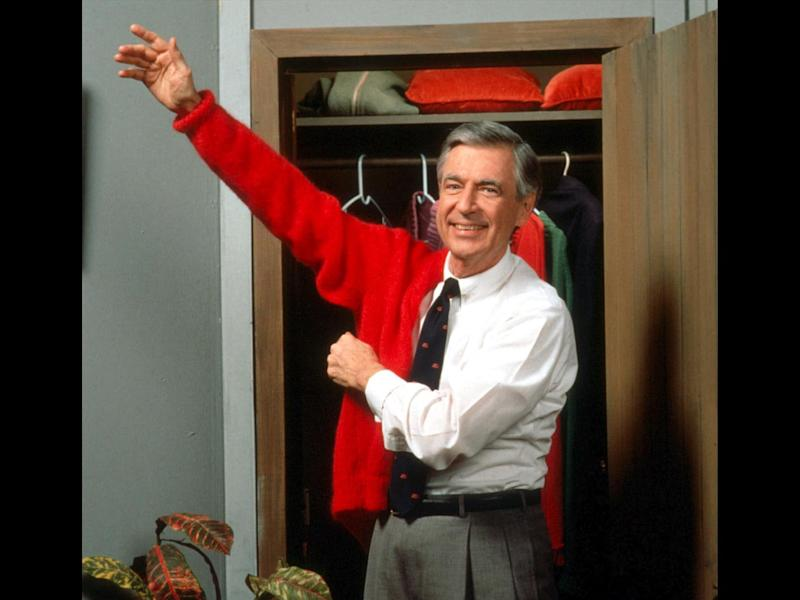 "Fred Rogers, as host of tv show ""Mister Rogers' Neighborhood"", puts on his red sweater, photo on black"