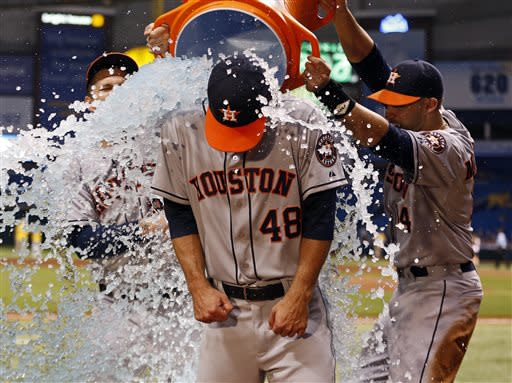 Houston Astros starting pitcher Jarred Cosart (48) is doused by teammates Brandon Barnes, left, and J.D. Martinez during a TV interview following his win in his major league debut of a baseball game against the Tampa Bay Rays, Friday, July 12, 2013, in St. Petersburg, Fla. The Astros won 2-1. (AP Photo/Mike Carlson)