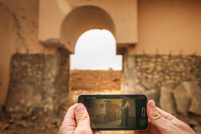 A smartphone with a picture of the ancient ruins of Nimrud, superimposed against the current state of the ruins following their recapture by Iraqi forces on November 13, 2016 (AFP Photo/Safin Hamed)