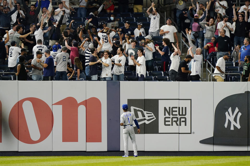 Kansas City Royals center fielder Jarrod Dyson (1) watches as a fan holds the ball up after catching a game-tying, solo home run by New York Yankees Gary Sanchez during the ninth inning of a baseball game, Wednesday, June 23, 2021, at Yankee Stadium in New York. (AP Photo/Kathy Willens)