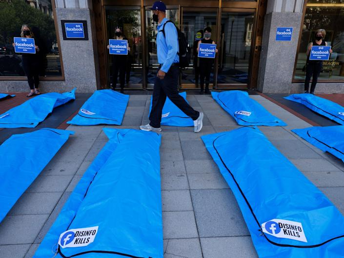 """a pedestrian walks through a protest between two rows of blue body bags that read """"disinfo kills."""" the bags are surrounded by activists holding signs that read """"facebook disinformation kills"""""""