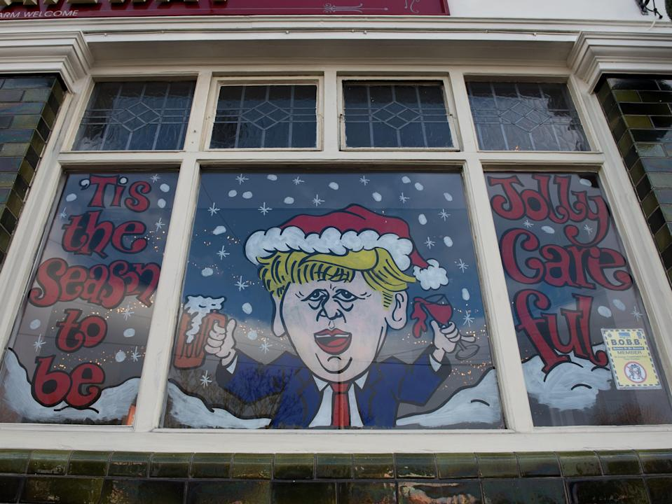 <p>A humorous decorated window on The Railway pub showing a caricature of Boris Johnson and the words 'Tis the season to be jolly careful'</p> (Getty)