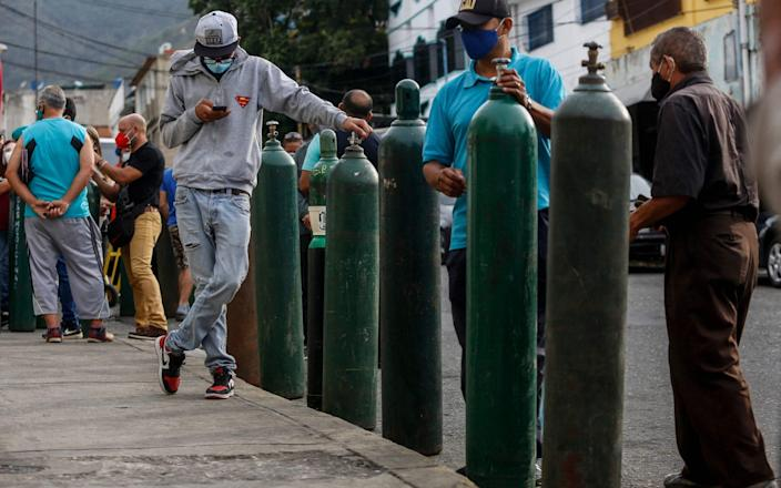 Brazilians queue to refill oxygen cylinders to be used by coronavirus patients in Caracas - Pedro Rances Mattey/AFP via Getty