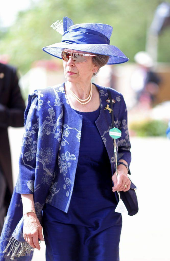 """<p>Princess Anne arrived for the day's races wearing a royal blue ensemble, a pair of sporty <a href=""""https://www.townandcountrymag.com/society/tradition/g36395845/royal-family-favorite-sunglasses-brands/#:~:text=The%20Royal%20Family's%20Favorite%20Sunglasses&text=If%20there's%20one%20brand%20the,on%2C%20it's%20Ray%2DBan."""" rel=""""nofollow noopener"""" target=""""_blank"""" data-ylk=""""slk:sunglasses"""" class=""""link rapid-noclick-resp"""">sunglasses</a>, and a horse-themed brooch.</p>"""