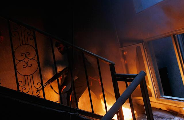 <p>A libyan rebel fighter runs up a burning stairwell during an effort to dislodge some ensconced government loyalist troops who were firing on them from an upstairs room during house-to-house fighting on Tripoli Street in downtown Misrata April 20, 2011 in Misrata, Libya. (Photo by Chris Hondros/Getty Images) </p>