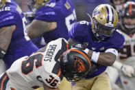 Rainwater flies as Washington running back Richard Newton, right, is hit by Oregon State linebacker Omar Speights during the first half of an NCAA college football game Saturday, Nov. 14, 2020, in Seattle. (AP Photo/Ted S. Warren)