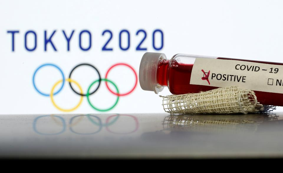 Fake blood in seen in test tubes labelled with coronavirus disease (COVID-19) in front of a displayed Tokyo 2020 Olympics logo in this illustration taken March 19, 2020. REUTERS/Dado Ruvic/Illustration