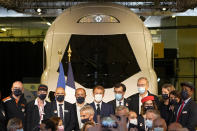 French President Emmanuel Macron, center, and other executives pose in front of a life-size replica of the next high-speed train TGV, at the Gare de Lyon station Friday, Sept. 17, 2021 in Paris. France unveils a super-fast, climate-friendly train of the future, the next generation of its high-speed TGV trains that have been emulated around the world. (AP Photo/Michel Euler, Pool)