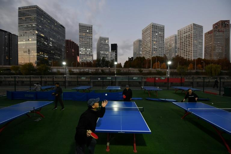 Table tennis enthusiasts play at a park opposite the central business district in Beijing