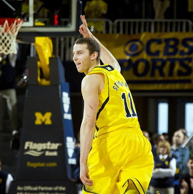 Michigan guard Nik Stauskas (11) reacts by holding up three fingers to celebrate his 3-pointer in the second half of an NCAA college basketball game against Michigan State at Crisler Center, Sunday, Feb. 23, 2014, in Ann Arbor, Mich.. Michigan won 79-70. (AP Photo/Tony Ding)
