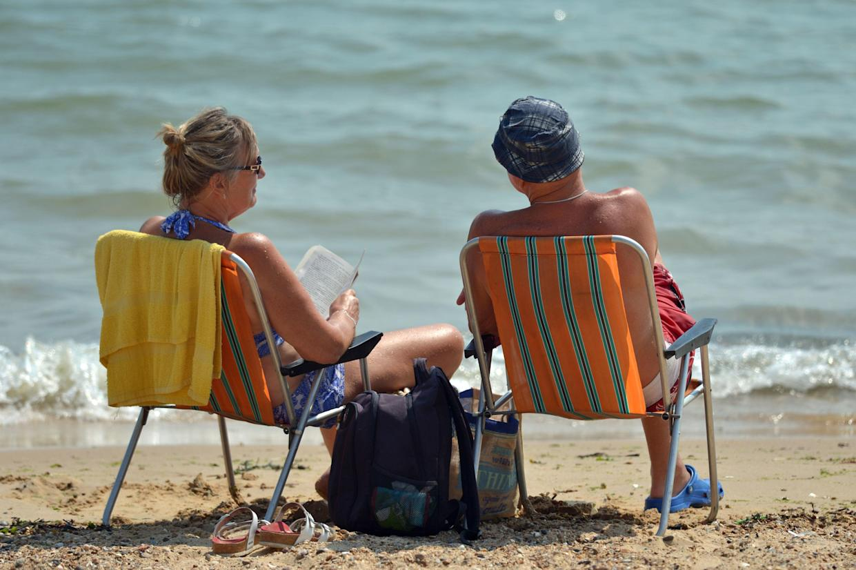 A couple relaxes on the beach at Clacton-on-Sea in Essex. (PA Images)
