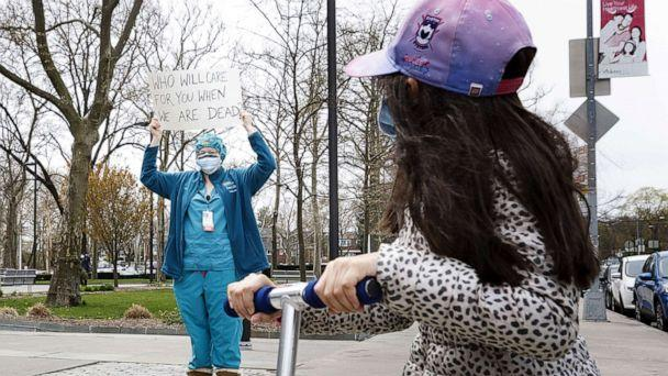 PHOTO: A child on a scooter looks at a nurse at Jacobi Medical Center participating in a rally to protest their lack of personal protective equipment, PPE, and institutional support in the Bronx borough of New York, April 17, 2020. (Justin Lane/EPA via Shutterstock, FILE)