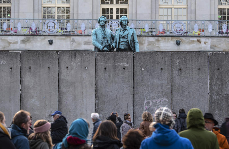 A wall, an art performance of the National Theatre Weimar, stand in front of the memorial of German poets Johann Wolfgang von Goethe, left, and Friedrich Schiller, right, prior the 30th anniversary of falling Berlin wall in Weimar, Germany, Wednesday, Oct. 30, 2019. With the temporary installation of 17 wall elements, the National Theatre recall the events of autumn 1989. The artist Christina Wildgrube designs this 'wall'. Unlike the former Belin wall, the art project should not create a long-term separation, but bring people together. (AP Photo/Jens Meyer)