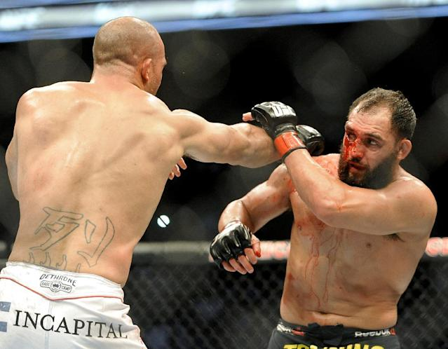 Johny Hendricks blocks a punch from Robbie Lawler during a UFC 171 mixed martial arts welterweight title bout, Saturday, March 15, 2014, in Dallas. Hendricks won by decision. (AP Photo/Matt Strasen)