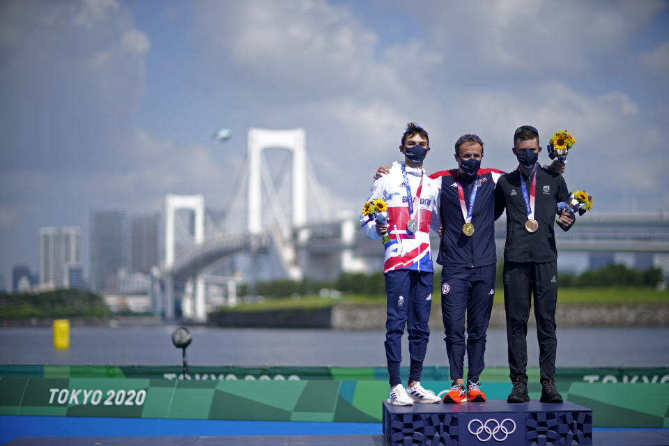 Gold medal winner Kristian Blummenfelt of Norway, center, poses with silver medalist Alex Yee of Great Britain, left, and bronze medalist Hayden Wilde of New Zealand during a medal ceremony for the men's individual triathlon at the 2020 Summer Olympics, Monday, July 26, 2021, in Tokyo, Japan. (AP Photo/David Goldman)