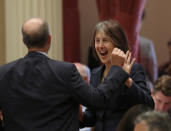"""Sen. Nancy Skinner, D-Berkeley, celebrates with Sen. Steven Glazer, D-Orinda, after her measure to let athletes at California colleges hire agents and sign endorsement deals was approved by the Senate in Sacramento, Calif., Wednesday, Sept. 11, 2019. The bill now goes to Gov. Gavin Newsom, who has not said whether he will sign it. But the NCAA Board Of Governors is already urging him not to, sending him a letter Wednesday saying the bill """"would erase the critical distinction between college and professional athletics"""" and would have drastic consequences for California's colleges and universities. (AP Photo/Rich Pedroncelli)"""