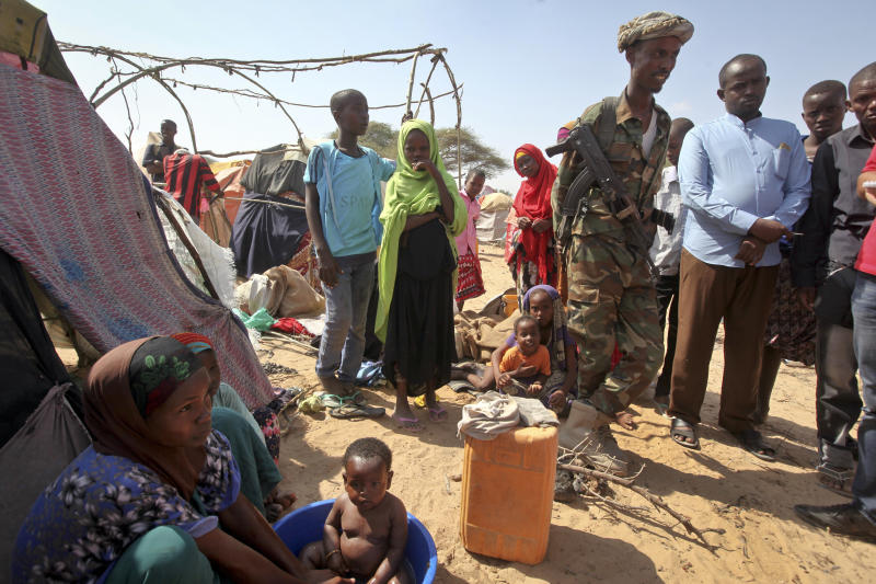 In this photo March 28, 2017, photo, a Somali soldier provides security as newly displaced Somalis gather at a camp in the Garasbaley area on the outskirts of Mogadishu, Somalia. Drought-stricken families facing a hunger crisis are on the move, trying to reach international aid agencies that cannot distribute food in areas under the control of al-Shabab, Somalia's homegrown Islamic extremist rebels who are affiliated to al-Qaida. Week by week, country by country, the Pentagon is quietly seizing more control over warfighting decisions, sending hundreds of more troops to war with little public debate and seeking greater authority to battle extremists across the Middle East and Africa. This week it was Somalia, where President Donald Trump gave the U.S. military more authority to conduct offensive airstrikes on al-Qaida-linked militants.(AP Photo/Farah Abdi Warsameh)