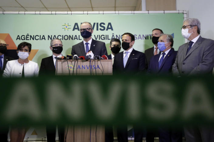 The Director of Brazil's National Health Surveillance Agency Antonio Barra speaks at a press conference regarding the CoronaVac vaccine, flanked by Sao Paulo Gov. Joao Doria, right center, in Brasilia, Brazil, Wednesday, Oct. 21, 2020. Brazil's President Jair Bolsonaro rejected on Wednesday the announced purchase of 46 million doses of the potential vaccine being developed by a Chinese company and tested in Sao Paulo, a state governed by his political rival, prompting concern he was allowing politics to steer public health decisions. (AP Photo/Eraldo Peres)