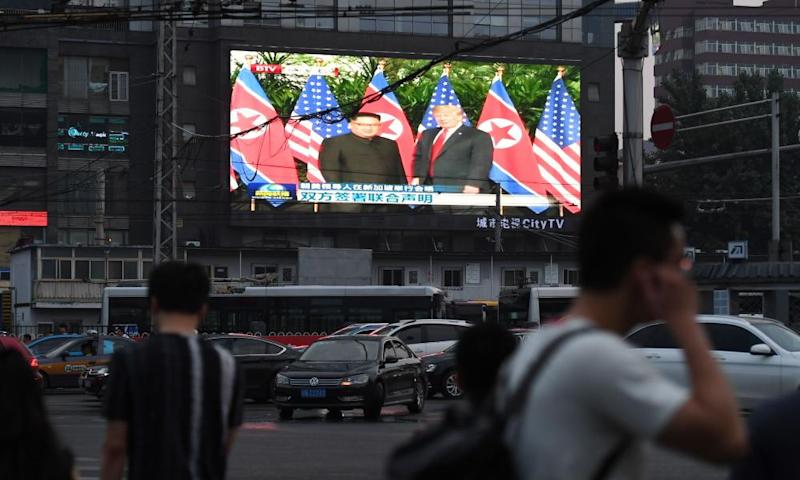 A large screen shows news footage of the summit meeting in Singapore between US President Donald Trump and North Korean leader Kim Jong-un, in Beijing