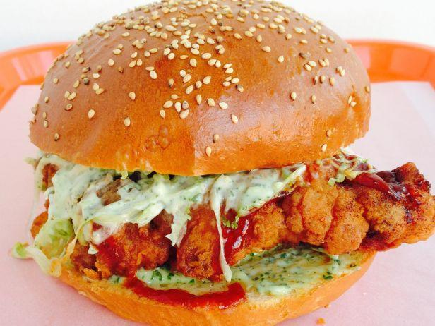 """<p><b>The Sandwich: Super Cluckin' Sunday Fried Chicken Sandwich.</b>The good news is the Super Cluckin' Fried Chicken sandwich is so addictive it has a cult following. The bad news is you can get it only once a month, on Super Cluckin' Sunday, when <a href=""""http://www.foodnetwork.com/restaurants/ma/brookline/cuttys-restaurant2.html?oc=PTNR-YahooFood-FN-coast_to_coast_fried_chicken"""">Cutty's</a> scraps its regular menu for just one between-the-bread beauty. """"We love the idea of a fast-food fried chicken sandwich, but we use awesome ingredients — nothing creepy, nothing to feel gross about,"""" says chef and co-owner Rachel Kelsey. Her recipe calls for housemade ranch dressing flecked with fresh herbs and tangy BBQ sauce, as well as shredded iceberg lettuce and Vidalia onion on griddled sesame bread. Customers start lining up at the Brookline sandwich shop at 9 a.m. in anticipation of the 10 a.m. opening.<i>(Photo courtesy of Cutty's)</i></p>"""