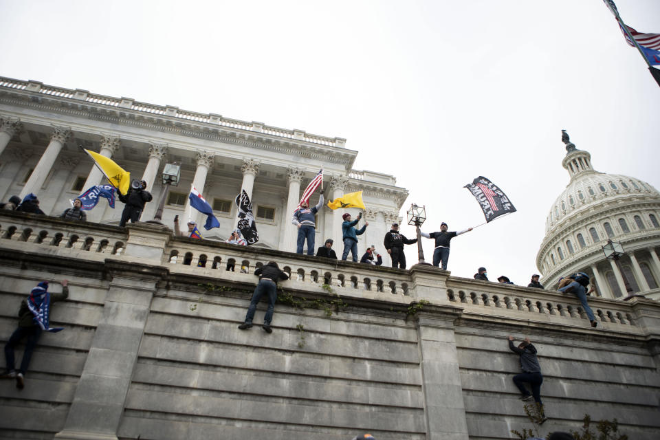 FILE - In this Wednesday, Jan. 6, 2021, file photo, supporters of President Donald Trump climb the west wall of the the U.S. Capitol on in Washington. Lies, misinformation and conspiracy theories related to the 2020 election are gaining traction among local, county and state Republicans, who are using their online platforms to disseminate many of the same dangerous messages that led to the violent insurrection at the Capitol last month. (AP Photo/Jose Luis Magana)