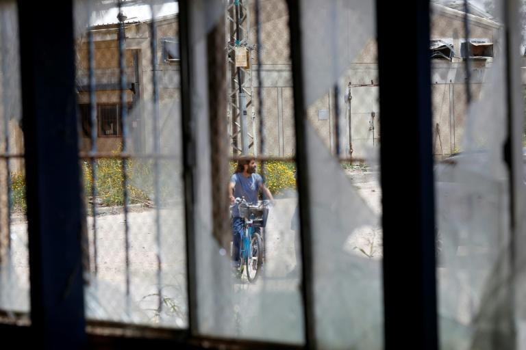 A man rides a bicycle in front of a building in the Kissufim kibbutz in southern Israel bearing traces of rockets fired from the Gaza Strip