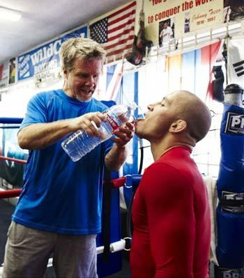 Freddie Roach helps Georges St. Pierre rehyrdate during a break in St. Pierre's Monday workout at Hollywood's Wild Card gym